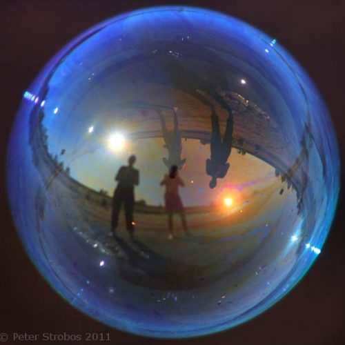 Figures reflected in a blue soap bubble.